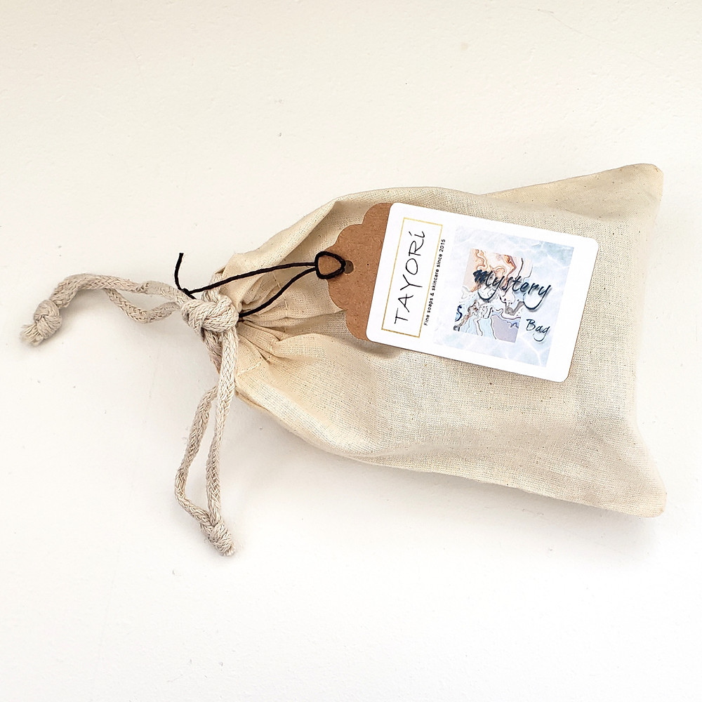 Natural cotton bag with Mystery Bag label which holds 3 bars of soap but you can't see them, to maintain the mystery