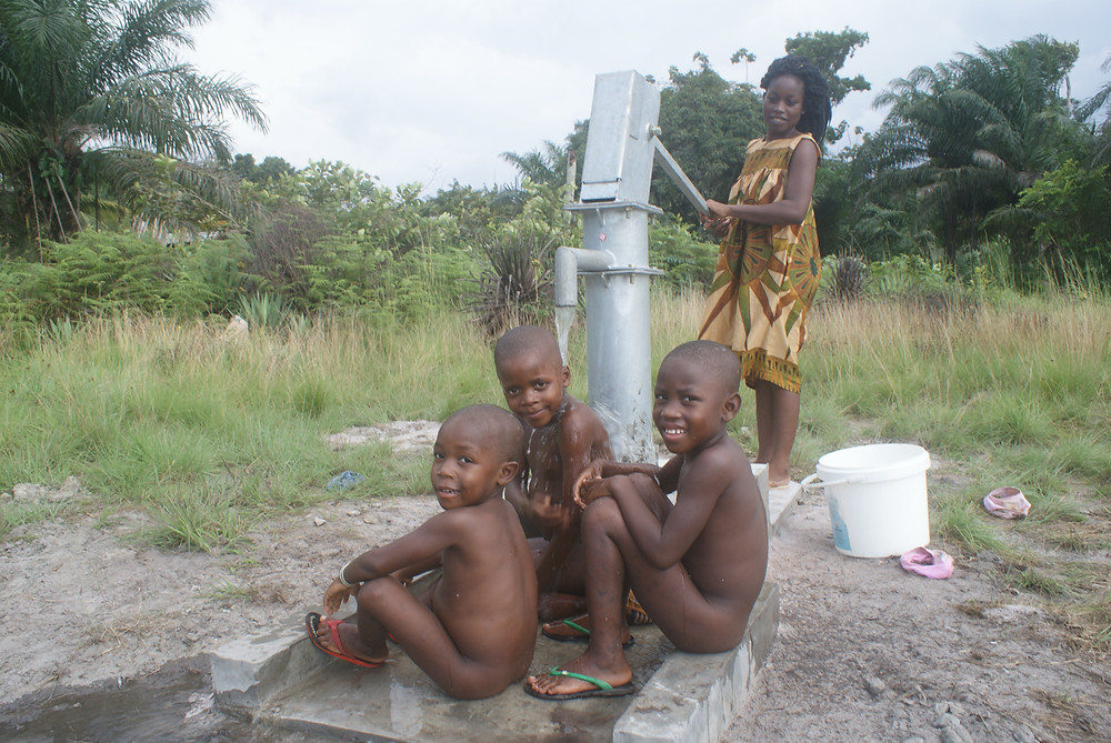 Boys cooling off at the local water well