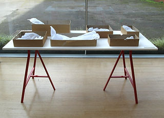 white tissue paper sculpture body parts imprints in archive boxes on a table