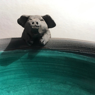 Pig bowl in black clay with teal glaze