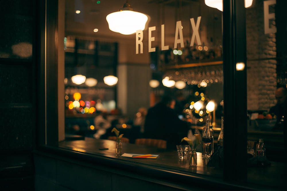 "Image of restaurant scene, as viewed through window. There is a person inside at a table in the background, in the foreground, there is the word ""relax"" in gold capital letters on a window"