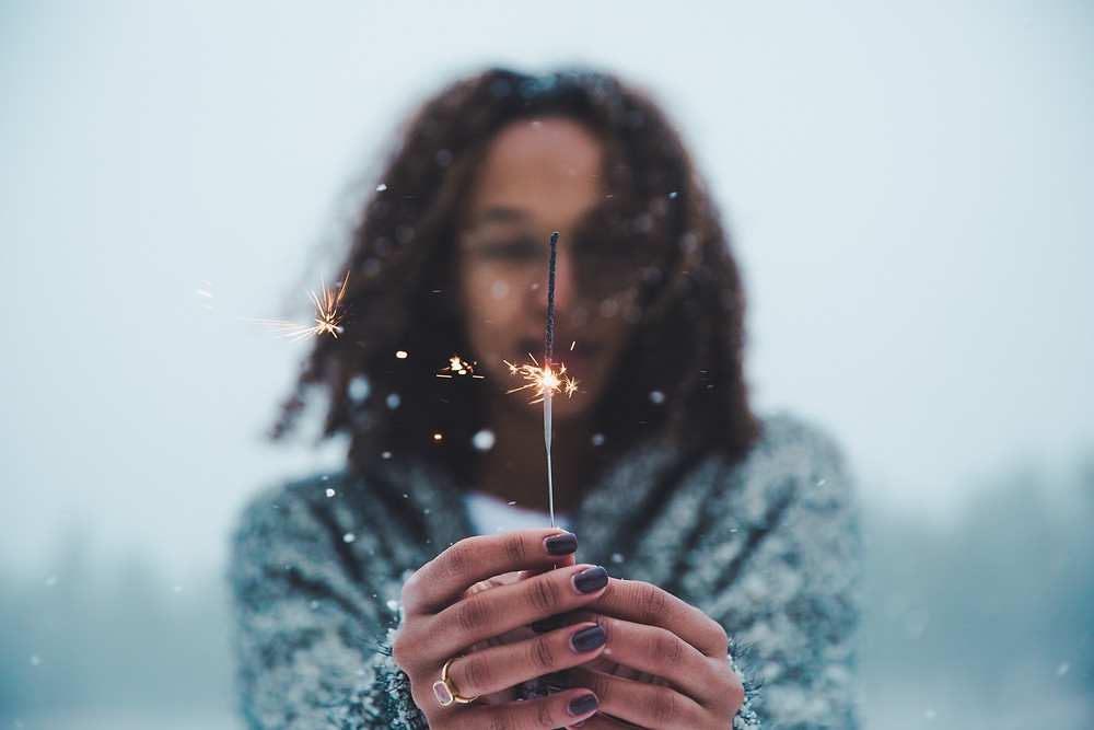 Brown person with dark, long, curly hair standing outside. Their face is blurry, as is the background. Their hands are outstretched in the foreground, holding a half-burned sparkler. Their fingernails are painted a dark color and they are wearing a ring on their left ringfinger.