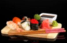 Sushi hosomakis et nigiris sur plateau de bois avec baguettes