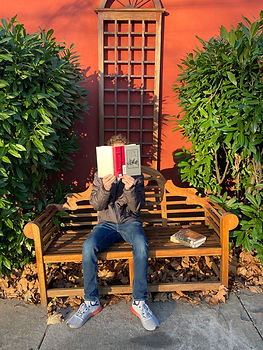 """A young man sitting on a bench outside reading the book """"Ben-Hur"""""""