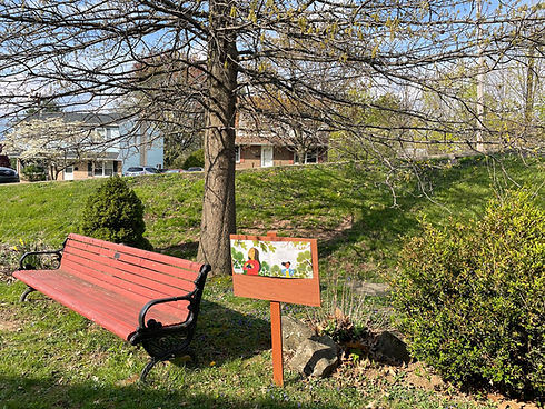 """A bench in a garden next to a wooden sign featuring a page from the book """"Ruby's Birds"""""""