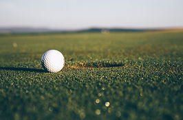 A picture of a golf ball next to a golf hole