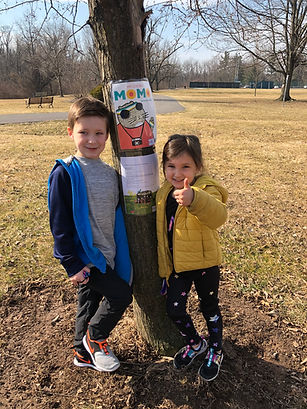 """Two children in front of a tree displaying pages from the book """"My Cousin Momo"""""""