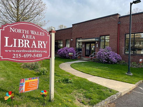 A picture of the library sign with the library entrance in the background.