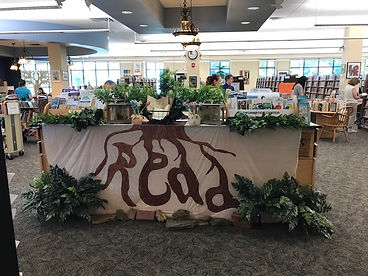 """The library circulation desk covered in plants with a large sign painted with tree roots that spelled out """"read"""""""