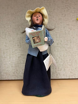A Byer's Choice doll of a woman dressed in traditional clothes holding a baby and a book