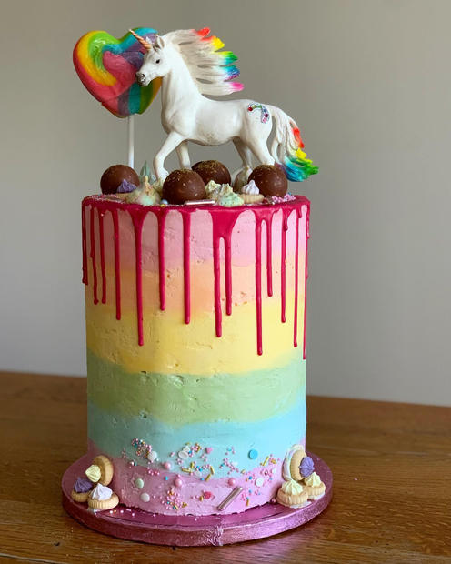 6 layer Nutella cake with rainbow buttercream, drip finish, sprinkles, lollipop and other decorations
