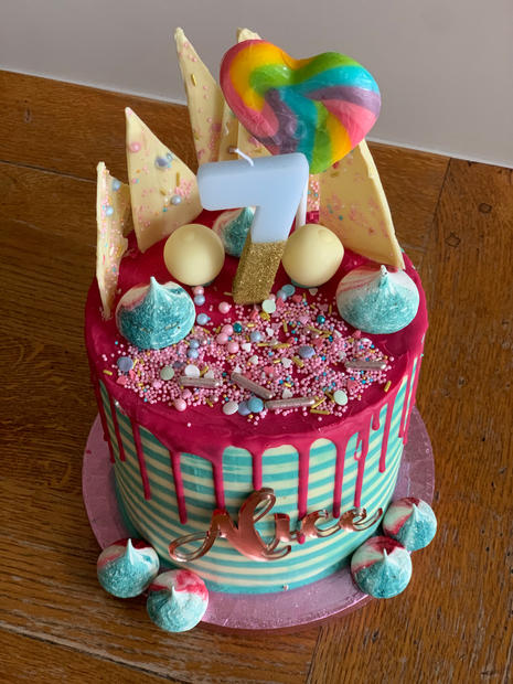 4 layer malted chocolate cake with striped buttercream, drip finish, name cake 'charm', sprinkles, mini meringues, chocolate shards, lollipop and chocolate decorations