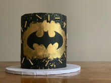 4 layer nutella cake, finished with buttercream in a batman design using gold edible paint and sprinkles