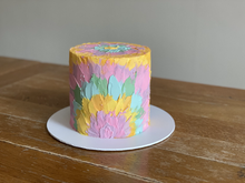 """4 layer, gluten free chocolate sponge, covered in American buttercream. Finished with rainbow buttercream in a """"tie dye"""" effect."""