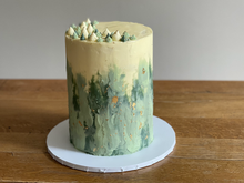 6 layer, Victoria sponge, covered in American buttercream. Finished with green abstract decoration, gold leaf and piping detail on top.