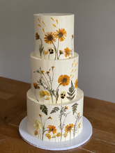 3 tiers, covered in swiss meringue buttercream and decorated with pressed flowers. Tier flavours were chocolate & salted caramel, vanilla & strawberry, and orange & lavender.