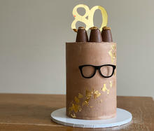 6 layer vanilla sponge, filled with dark chocolate ganache. Finished with chocolate swiss meringue buttercream, touches of gold leaf, custom acrylic glasses and topped with walnut whips