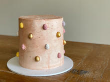 4 layer lemon cake, filled with lemon cream, finished with Swiss meringue buttercream, mini eggs and edible gold paint