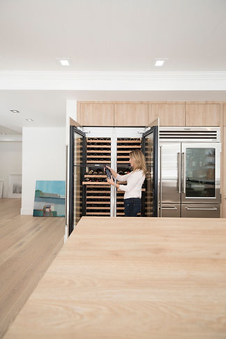 Leicht client in front of Subzero wine chillers and refrigerator. Bondi and Synthia door fronts.