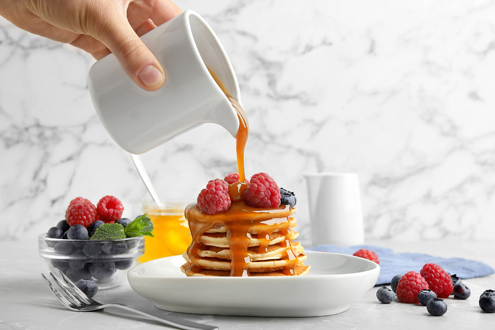 Woman pouring syrup onto fresh pancakes