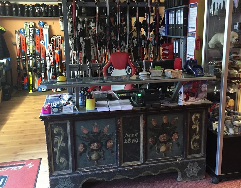 Empfang im Shop mit verschiedenen ausgestellten Ski und Snowboards
