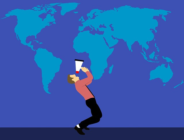 Man with a megaphone screaming at a giant world map