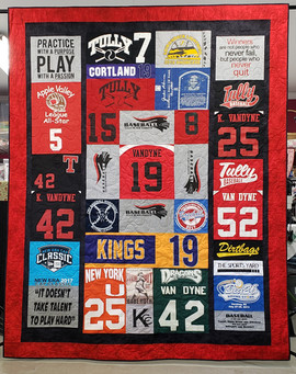 Full size Custom style T-shirt quilt with black sashing and red border.