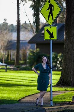 Woman standing next to a pedestrian sign.