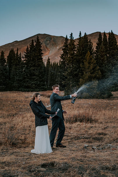 Bride and groom popping champagne on a mountain top, Breckenridge elopement, November mountain elopement, Colorado elopement photography