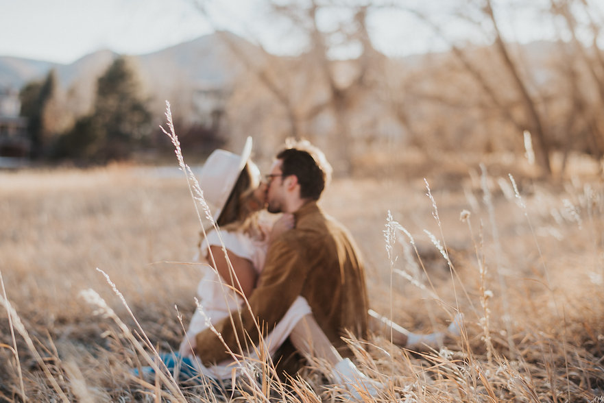 Hazy photo of sexy couple sitting in the grass kissing, Colorado couple, boho couple, Colorado couple photography, sexy couple photography