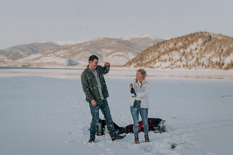 Newly engaged male and female couple popping champagne in the snow, snowy mountain proposal, winter engagement photos, Colorado engagement photography, Colorado proposal photography