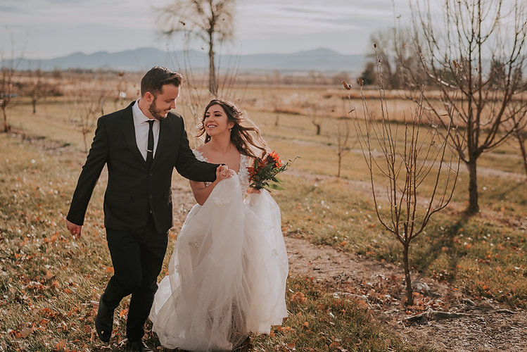 Bride and groom running and laughing through a vineyard, fall farm wedding, Colorado bride and groom, Colorado wedding photography, bride and groom candid photo