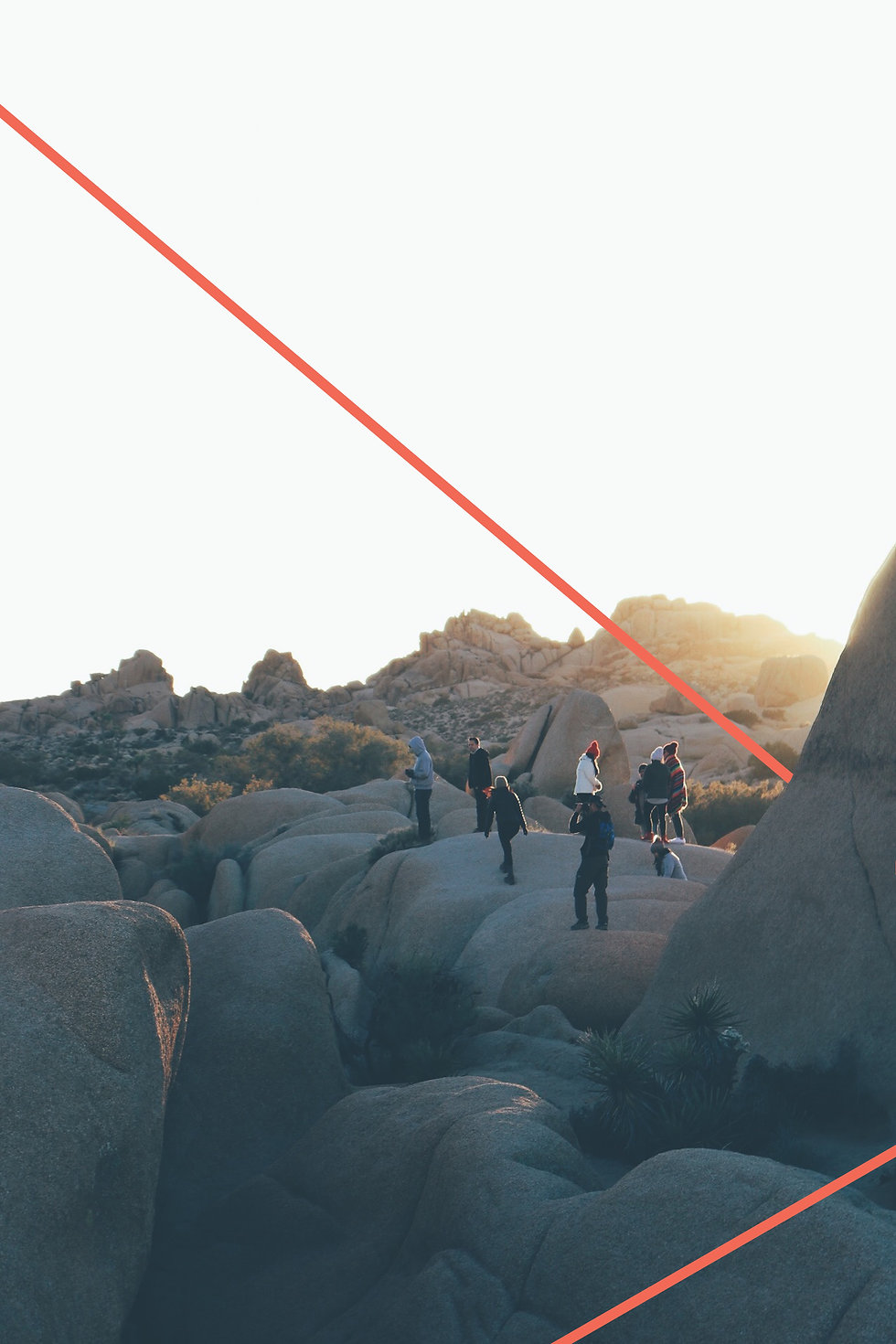 a group of adults standing on a bank of rocks during a sunset