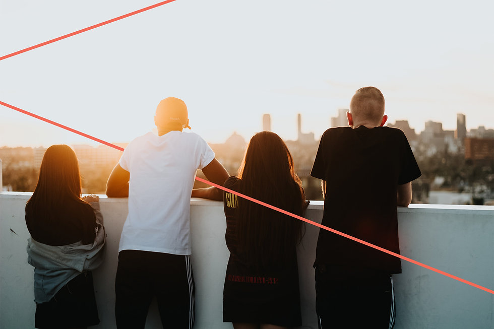 group of young adults leaning on the roof of a building. staring at the city skape and sunset