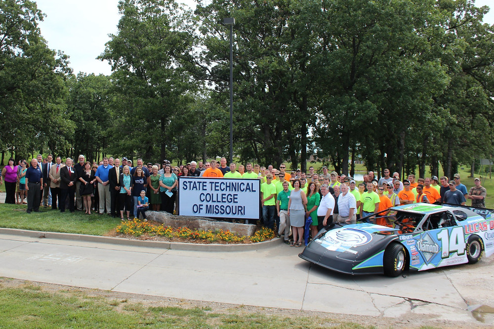 Students, administrators and supporters of the newly named State Technical College of Missouri gather around the new sign in front of the campus in Linn. Supporters include Associated Industries of Missouri president Ray McCarty (front row, left of the sign, dark suit, light tie). AIM supports State Tech's mission of supplying highly trained workers for the state's manufacturers.