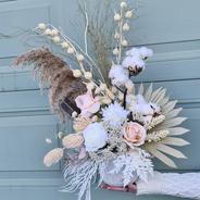Artificial arrangement with cottonball spray, fantasy seed spray, palm leaf, cream and white reflexed roses, fern and feather spray and pampas grass.