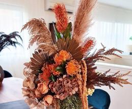 Artificial autumn orange arrangement in vase.