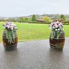 Wine barrel arrangements in blush pink and white.