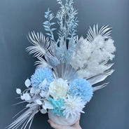 Baby blue arrangement. Silver palm leaves, blue and white chrysanthemum balls, white roses and preserved white fern.