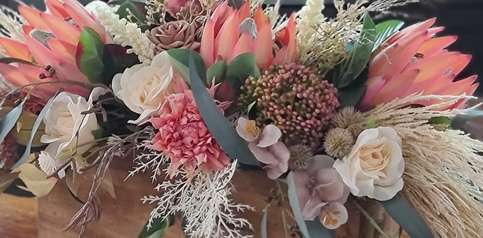 Table arrangement in natives. Blush pink and cream proteas and eucalyptus.