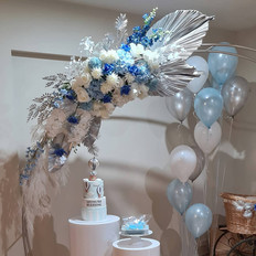 Steel arbor and blue and white flowers, silver palm leaves.