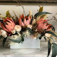 Faux flower arrangement. Peach proteas, cream roses, gum leaves, grevillas and fillers.