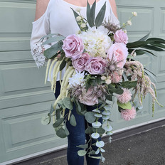 Artificial eclectic bridal bouquet in soft mauve and pinks.