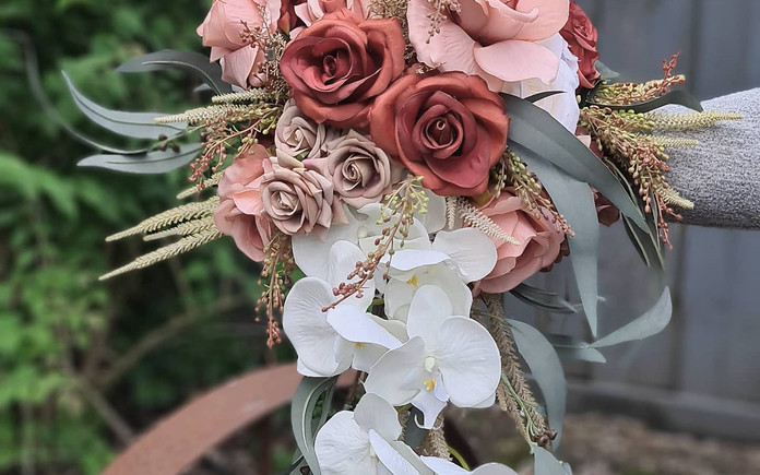 Cascading bridal bouquet with faux real touch roses, white orchids and gum leaves.