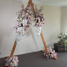 Triangle arbor with blush pink floral clouds.