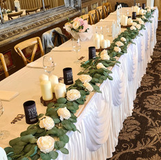 Eucalyptus garlands and ivory scatter roses.