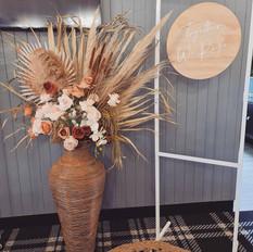 Boho chic pampas and palm leaf arrangement in cane floor standing vase.