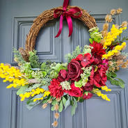 Wreath with silk red roses, red hydrangeas, yellow wattle and greenery.