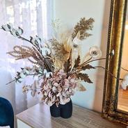 Whimsical faux flower arrangement in neutral tones.