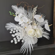 White faux flower arrangement. White roses, white anthuriums, white palm leaves, white orchids and white fantasy fillers.
